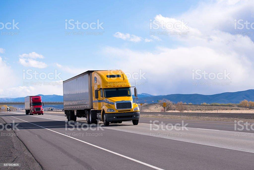 Caravan modern semi trucks on straight highway on plateau stock photo