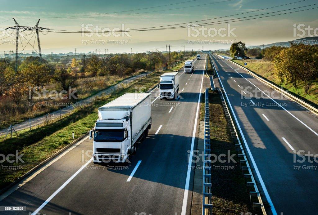 Caravan of white trucks on highway stock photo