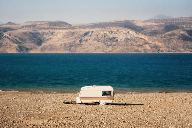 Caravan on shore of lake among desert and mountains, Uzbekistan stock photo