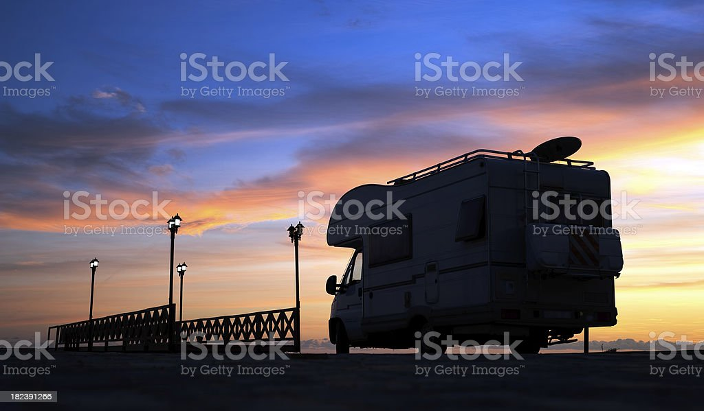 Caravan on the road and bridge at sunset royalty-free stock photo