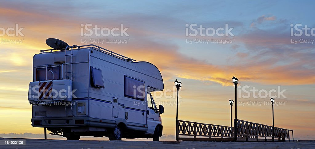 Caravan on the road at sunset royalty-free stock photo