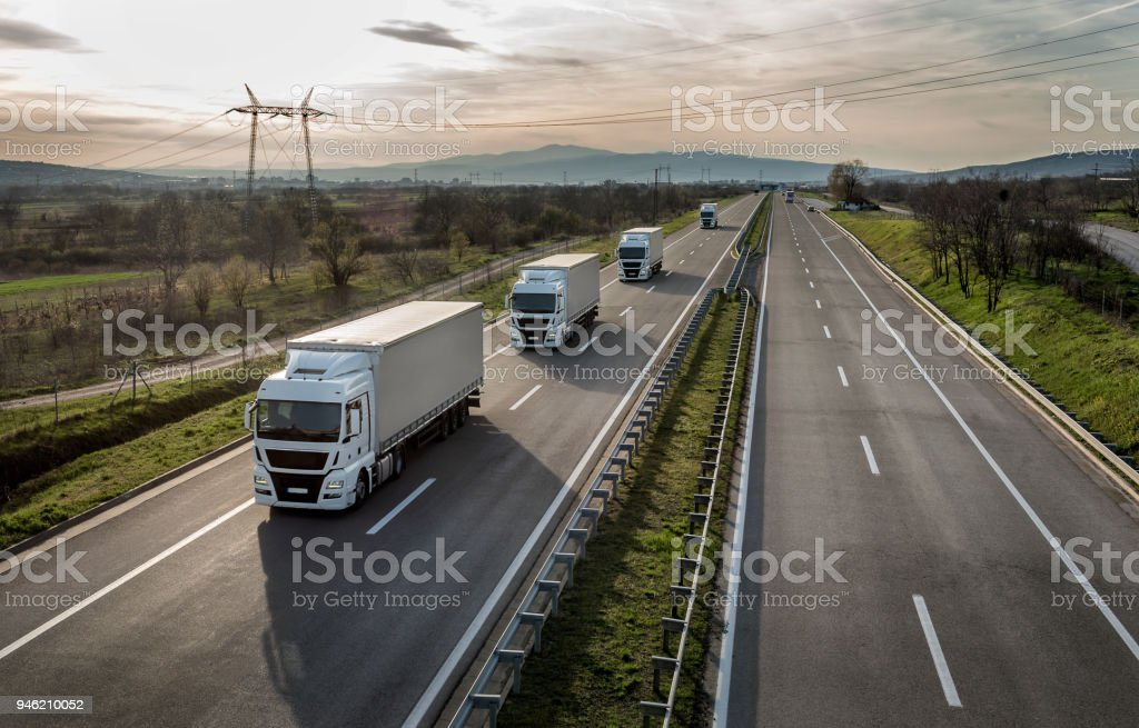 Caravan or convoy of trucks on highway Caravan or convoy of trucks in line on a country highway Agricultural Field Stock Photo