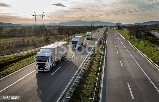 Caravan or convoy of trucks in line on a country highway
