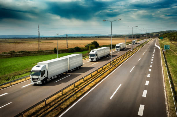 Caravan or convoy of White Lorry trucks on highway Caravan or convoy of White Lorry  trucks in line on a country highway caravan photos stock pictures, royalty-free photos & images