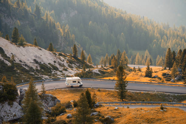 Caravan Caravan car travels on a mountain road at sunset motor home stock pictures, royalty-free photos & images