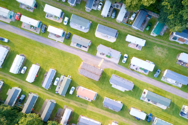 Caravan site park aerial view illuminated by summer sun Caravan site park aerial view illuminated by summer sun uk manufactured housing stock pictures, royalty-free photos & images