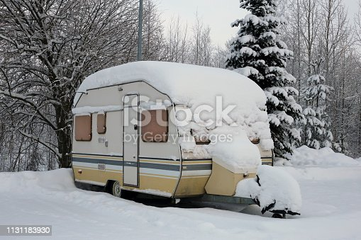 Caravan trailer in a parking lot next to a forest covered with snow during winter in Europe. The trailer is yellow and grey colored and there is snowy trees and snow around the trailer.