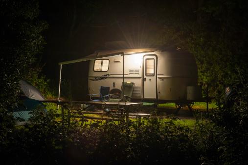 Caravan trailer glowing in forest camp site night