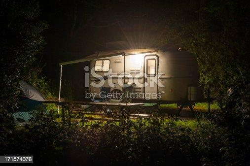 Compact travel trailer glowing with warm light through windows in a forest RV park in the Pacific Northwest of the USA. ProPhoto RGB profile for maximum color fidelity and gamut.