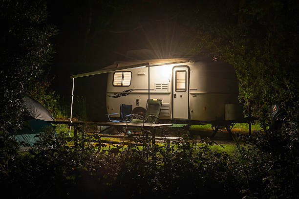 caravan trailer glowing in forest camp site night - caravan stockfoto's en -beelden