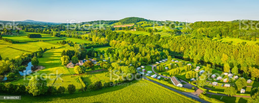 Caravan trailer park campsite nestled in green countryside aerial panorama stock photo
