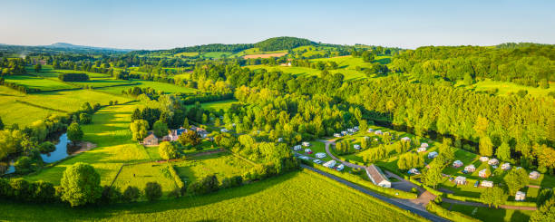 Caravan trailer park campsite nestled in green countryside aerial panorama Aerial panorama over caravan trailer park campsite nestled in a picturesque river valley meandering between rolling hills of patchwork pasture and green summer landscape. south wales stock pictures, royalty-free photos & images