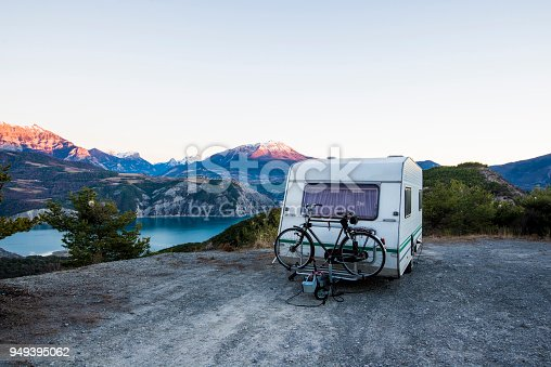 istock Caravan with a bike parked on a mountaintop with a view on the french Alps near lake Lac de Serre-Poncon 949395062