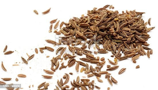 Scattered caraway seeds on white background.