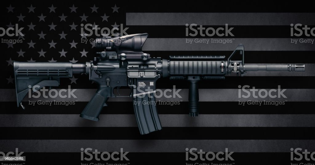 M4A1 Carbine Over USA Flag M4A1 Carbine with ACOG M150 optic commonly carried by US Military personnel, as well as US civilians in semi-auto configuration commonly known as the AR-15.  These were made by Colt Firearms and FN(Fabrique Nationale Herstal, FN America, FN Manufacturing).  Includes standard features such as pistol grip, Knights RAC forearm, collapsible stock, flash suppressor, and bayonet lug. AR-15 Stock Photo