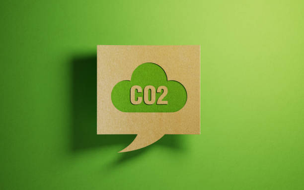 carbon emission icon on a chat bubble which is made of recycled paper over green background - anidride carbonica foto e immagini stock