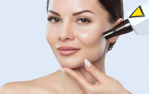 Carbon face peeling procedure in a beauty salon. Hardware cosmetology treatment. stock photo