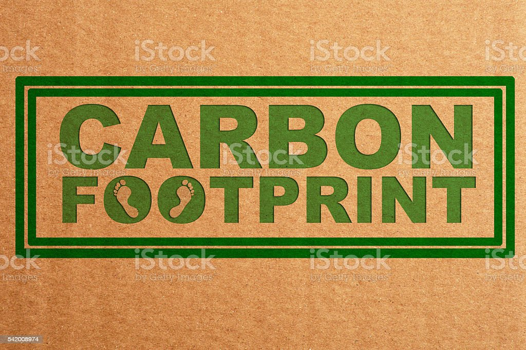 Carbon Footprint Written on Cardboard Background stock photo