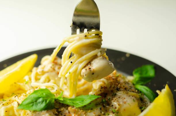 Carbonara, espaguete com queijo e molho de bacon defumado coberto com pedaços de peito de frango e queijo Regato - foto de acervo