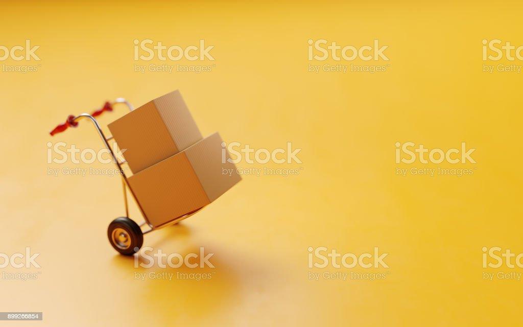 Kaart dozen op A Hand vrachtwagen op gele achtergrond foto