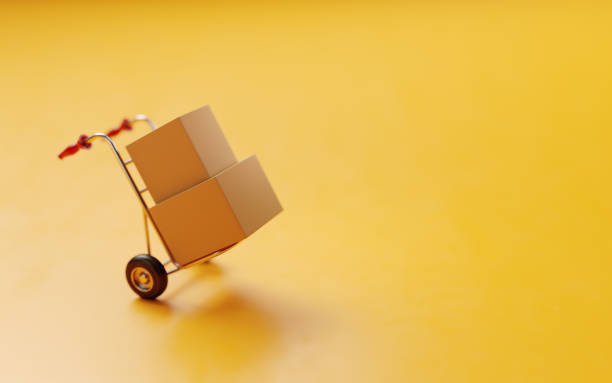 card boxes on a hand truck on yellow background - physical activity stock pictures, royalty-free photos & images