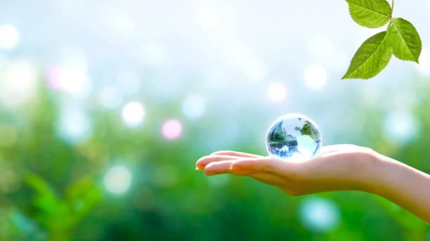 tarjeta para el concepto del día mundial de la tierra. globo de cristal azul cristal de la tierra en la mano humana y hoja verde sobre fondo borroso. ahorro de medio ambiente y concepto de planeta verde limpio. - lifestyle color background fotografías e imágenes de stock
