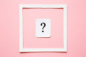 istock Card of question mark in white frame on pastel pink background. Soft light color. Women issues. Problem and solution concept. 1026435104