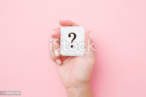 istock Card of question mark in young woman hand on pastel pink background. Concept of plans, thoughts or other good ideas for making decision. Close up. Top view. 1165882283