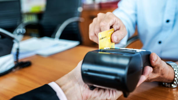 Card payments between businessmen via credit card machine in the office. stock photo