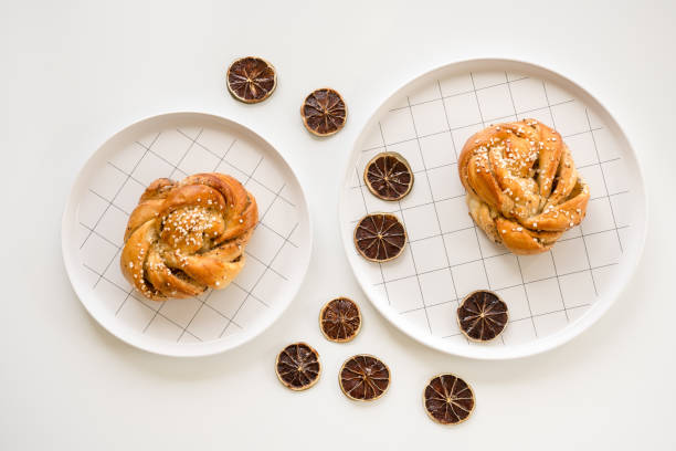 Cardamom buns decorated with dried lemon slices Traditional Scandinavian cardamom buns decorated with dried lemon slices. sweet bun stock pictures, royalty-free photos & images