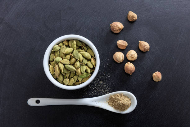 Cardamom in porcelain bowl and spoon Cardamom in porcelain bowl and spoon, black background cardamom stock pictures, royalty-free photos & images