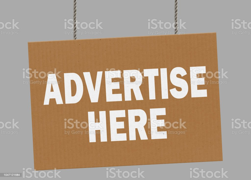 Cardboard advertise here sign hanging from ropes. Clipping path included so you can put your own background. stock photo