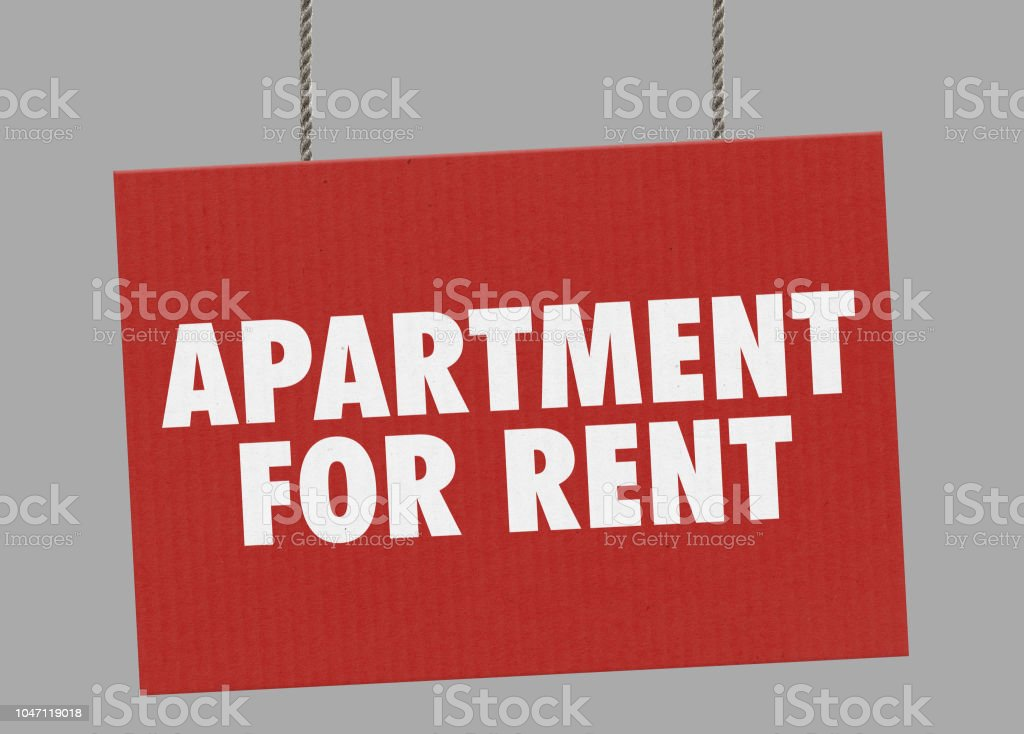Cardboard apartament for rent sign hanging from ropes. Clipping path included so you can put your own background. stock photo