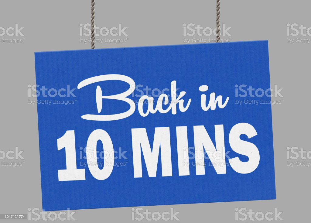 Cardboard back in 10 minutes sign hanging from ropes. Clipping path included so you can put your own background. stock photo