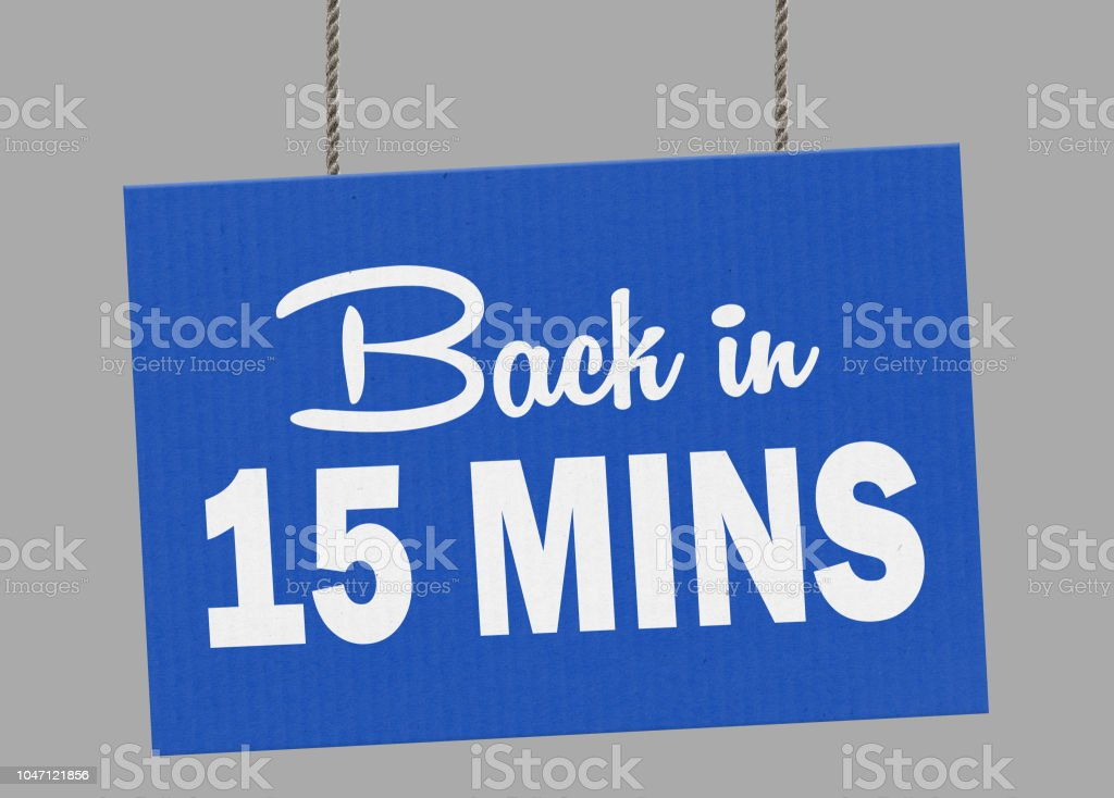 Cardboard back in 15 minutes sign hanging from ropes. Clipping path included so you can put your own background. stock photo
