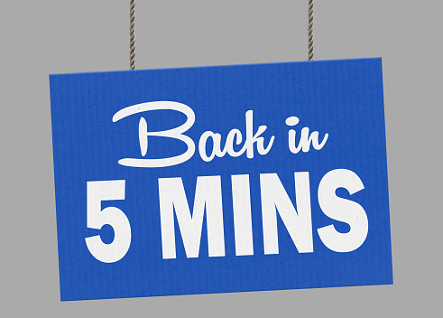 istock Cardboard back in 5 minutes sign hanging from ropes. Clipping path included so you can put your own background. 1047121768