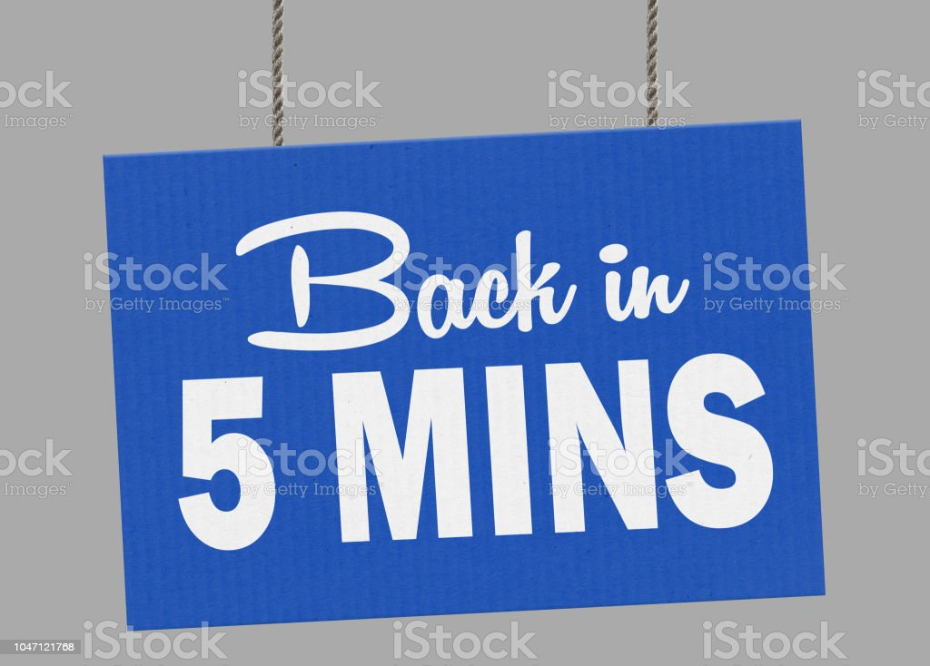 Cardboard back in 5 minutes sign hanging from ropes. Clipping path included so you can put your own background. stock photo