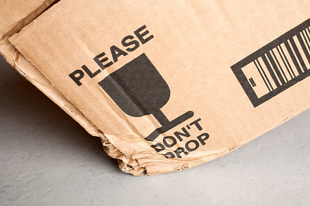 Cardboard Box Dropped Despite Warning Cardboard box with 'Please Don't Drop' notice dropped on hard tiled floor. despite stock pictures, royalty-free photos & images