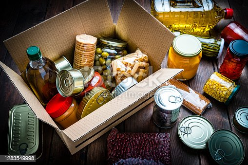High angle view of a cardboard box filled with multicolored non-perishable canned goods, conserves, sauces and oils shot on wooden table. The composition includes cooking oil bottle, pasta, crackers, preserves and tins. High resolution 42Mp studio digital capture taken with SONY A7rII and Zeiss Batis 40mm F2.0 CF lens