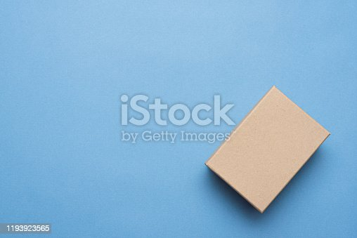 Brown closed cardboard box on blue background.