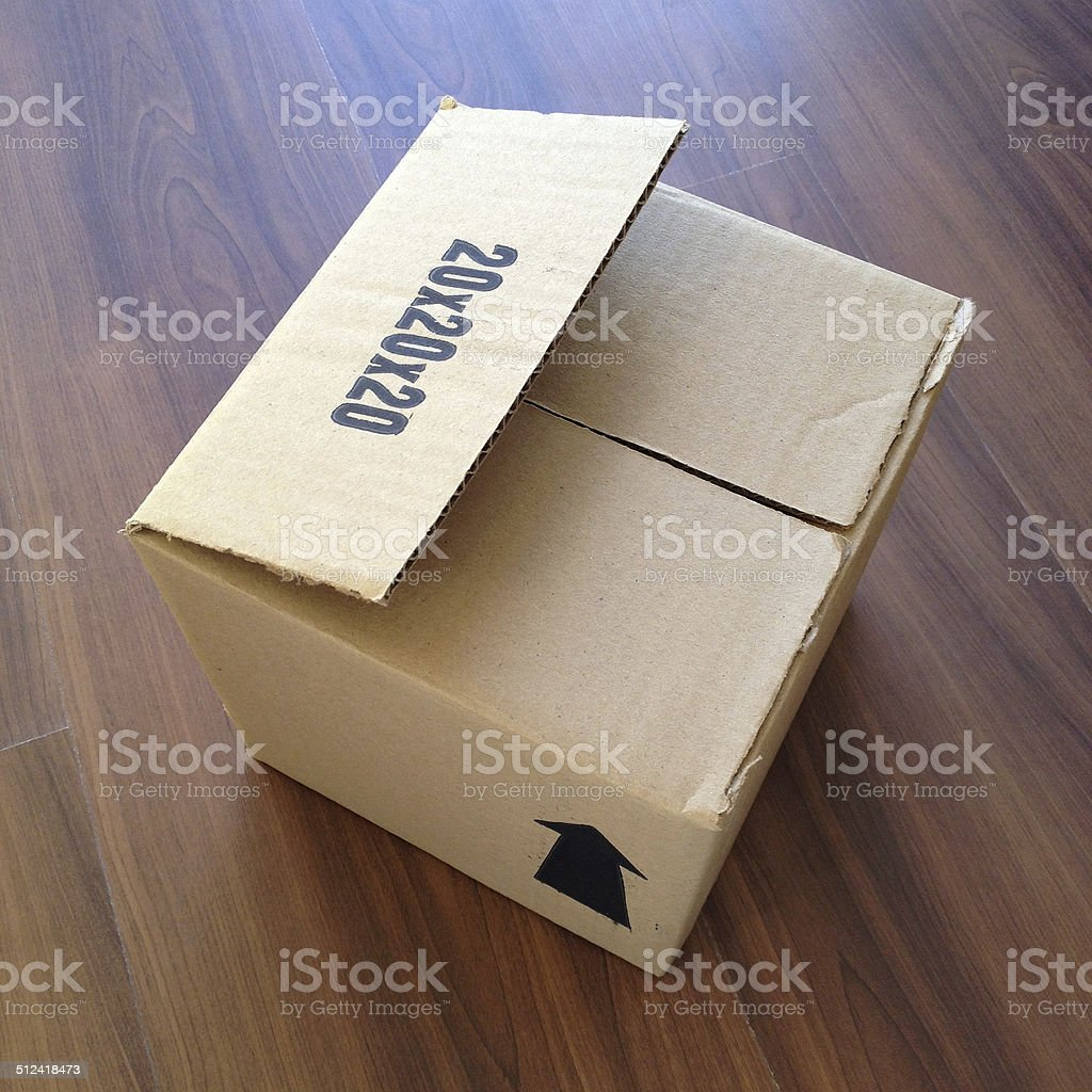 Cardboard box lying over wooden floor