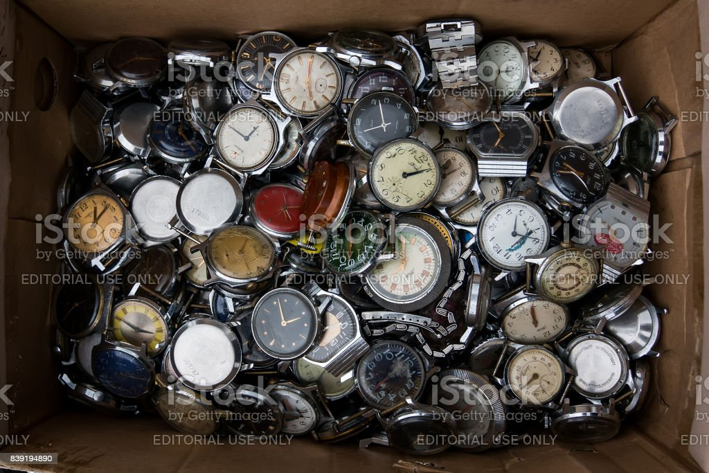 cardboard box with a large pile of old watches. stock photo