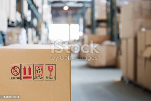 istock Cardboard box with goods on the background of a blurry modern warehouse 903449724