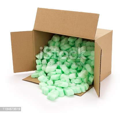 Brown open corrugated cardboard moving box, filled with green styrofoam pellets or packing peanuts falling out on white background. Contains clipping path.