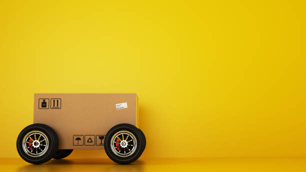 Cardboard box with racing wheels like a car on a yellow background. Fast shipping by road - foto stock
