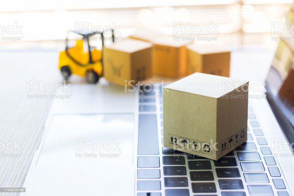 Cardboard box with symbols on laptop keyboard and mini forklift truck...