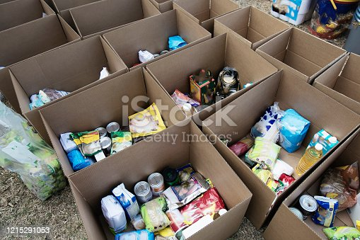 Cardboard boxes being filled with food donations for Coronavirus disaster relief.
