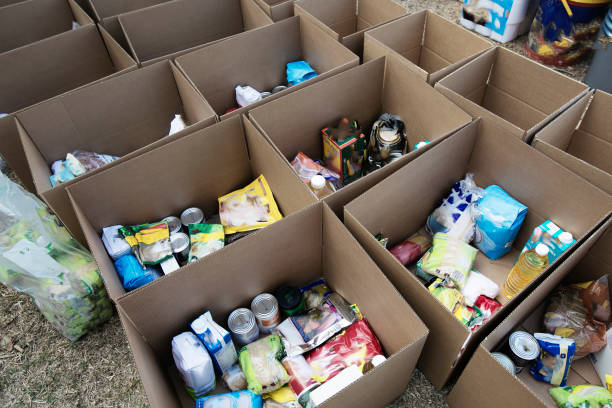 Cardboard boxes being filled with food donations stock photo