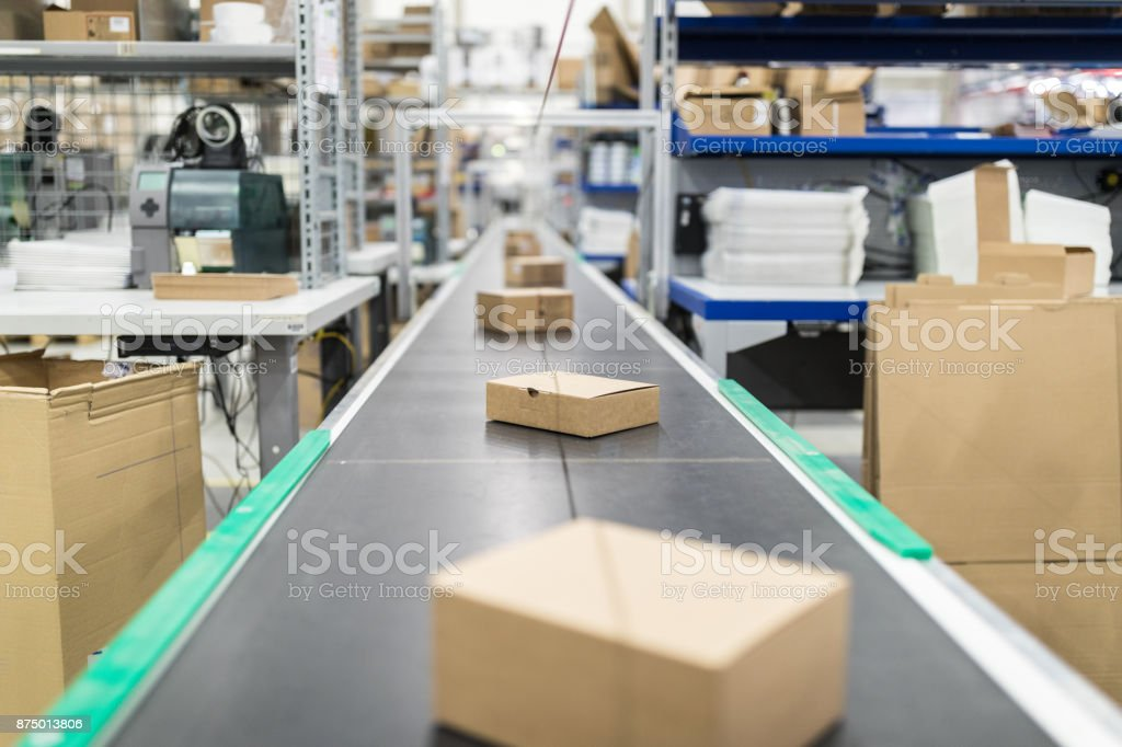 Cardboard boxes on conveyor belt at distribution warehouse royalty-free stock photo