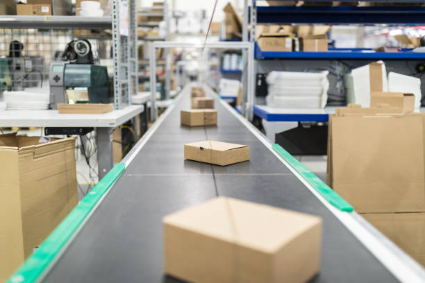 Cardboard boxes on conveyor belt at distribution warehouse stock photo